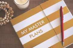 Golden straps diary with red pen, white candle and bracelet stock photo