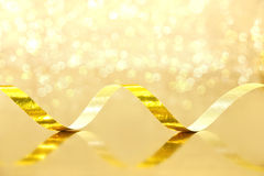 Golden Streamer on shiny background. Holiday background or greet. Ing card. Selective focus Royalty Free Stock Image