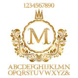 Golden striped letters and numbers with initial monogram in coat of arms form. Shining font and elements kit for logo design.  Royalty Free Stock Photos