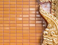 Golden stucco frame on the tiles wall. Stock Photo