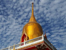 Golden Stupa soaring in cloudy sky Stock Images