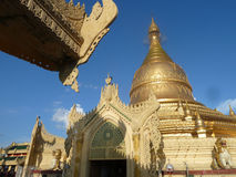 Golden Stupa Structure with Overhanding Eave in Foreground, Burm. Golden stupa structure shining in late afternoon sun in Burma (Myanmar), with overhanging eave Stock Photography
