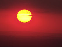 Golden sun. Beautiful yellow sun under red sky over the hills stock photo