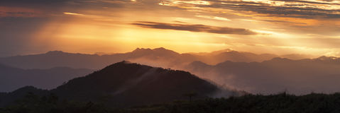 Golden Sun-ray on layers of mountains. Shot of the Golden Sun-rays shine on layering of mountains with Mists Stock Images