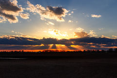 Golden Sun rays behind clouds sunset Royalty Free Stock Photo