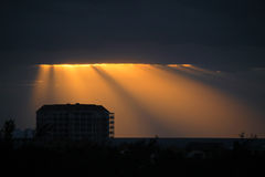 Golden sun rays bursting through the dark blue clouds Stock Photos