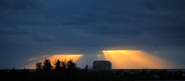 Golden sun rays bursting through the dark blue clouds Royalty Free Stock Images
