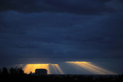 Golden sun rays bursting through the dark blue clouds Royalty Free Stock Photo