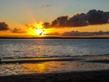 Sunsetting on beach, Point Chevalier, Auckland, New Zealand. A golden sun setting below the clouds over flowing water heading to the beach Stock Photo