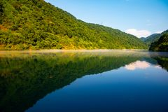 The golden sun shine on the green trees are on the hill,a reflection on the Calm lake,under the blue sky and white clouds stock image