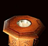 Golden sun shining on top of wooden baptismal font stock photo