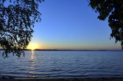 Golden sun sinks over the lake in the evening Royalty Free Stock Image