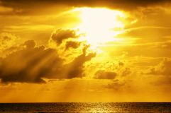 Golden sunlight through clouds. On the sea Stock Photography