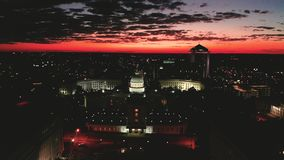 Dexter Avenue leads to the classic statehouse in downtown Montgomery Alabama. Golden sunlight reaches the horizon showing around the capital statehouse in stock footage