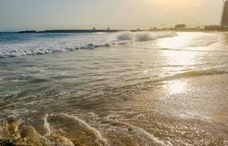 Golden sunlight reflecting on a beach in Lagos, Nigeria. Sun shining in the evening - waves breaking on the shore. Holiday blue sky tropical travel sunshine royalty free stock photo