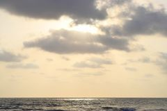 Golden Sunrays coming Through Dark Clouds and Falling over Ocean Royalty Free Stock Image