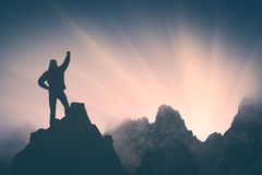 Golden sunrise above Titnuldi. Instagram stylisation. Man standing on a cliffs edge with raised hand against sunrise above Titnuldi mountain. Caucasus, Georgia Royalty Free Stock Images