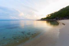 Golden sunrise behind the headland on desert exotic beach Royalty Free Stock Image