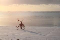 Golden sunrise and fisherman on a bike Royalty Free Stock Image