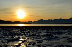 Golden sunrise over blue fjord and snowy mountain with reflection on thick ice royalty free stock images