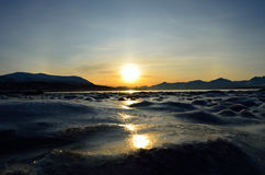 Golden sunrise over blue fjord and snowy mountain with reflection on thick ice stock images
