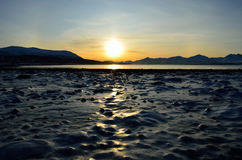Golden sunrise over blue fjord and snowy mountain with reflection on thick frozen sea shore ice stock photography