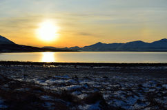 Golden sunrise over blue fjord and snowy mountain with reflection on thick ice stock image
