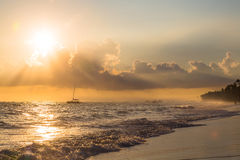 Golden sunrise over ocean with alone boat in Dominican Republic Stock Images