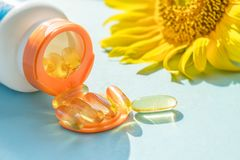 Golden Sunscreen pills with bottle and sunflower on blue background in sunlight. Dietary supplements, protect skin from the sun.