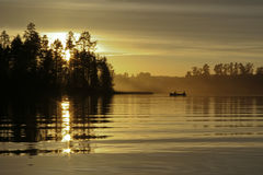 Golden sunset. Golden scenery with boat and two people Royalty Free Stock Images
