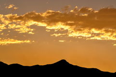 Golden sunset against mountain silhouette Royalty Free Stock Photos