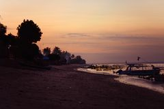 Golden sunset in Bali against the background of boats and waves. With trees and sand Stock Photo