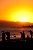 GOLDEN SUNSET ON THE BEACH. Silhouette of friends taking photos on the beach during sunset time royalty free stock image