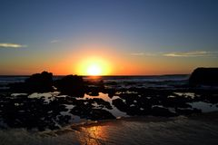 Golden sunset at a beach with rocks and rock pools. Golden sunset at a beach with rocks, waves and rock pools Stock Photos