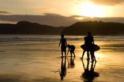 Golden Sunset Beach Silhouettes. Beach sunset with silhouettes of people and surfboard royalty free stock photos