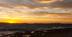 Golden sunset behind Conejera Islands.  Choppy waters of Balearic sea churns waves on rocks along shore.   View of Conejera Island Royalty Free Stock Photo