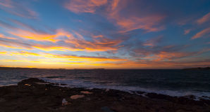 Golden sunset behind Conejera Islands.  Choppy waters of Balearic sea churns waves on rocks along shore.   View of Conejera Island Royalty Free Stock Photography
