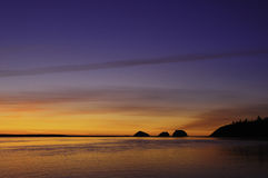 Golden Sunset behind Three Arch Rocks Stock Images