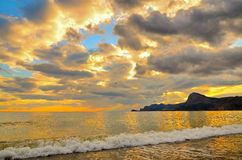 Golden sunset on the Black sea coast in Crimea, sea wave. At sunset a beautiful cloudy sky is painted in gold and blue. Sea wave is incident on the beach. On royalty free stock images