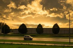 Golden sunset. Car passing by on a background of some nice copper colored clouds Stock Photo