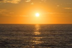Golden sunset centered over empty ocean Royalty Free Stock Images