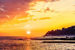 Golden sunset with distant spurdikes on Black Sea coast in Sochi, Russia. Beautiful scenic summer seascape royalty free stock images