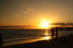 Golden Sunset. Friends chat at sunset on a Hawaiian beach Stock Images