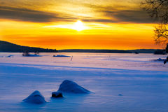 Golden sunset on a frozen lake. Golden sunset on a snowy, frozen lake royalty free stock photography