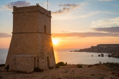 Golden sunset at Ghajn Tuffieha Tower. Beautiful golden sunset at Ghajn Tuffieha Tower, above Golden Bay, ancient watchtower built by the Knights of St. John Royalty Free Stock Image