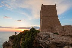Golden sunset at Ghajn Tuffieha Tower. Beautiful golden sunset at Ghajn Tuffieha Tower, above Golden Bay, ancient watchtower built by the Knights of St. John Royalty Free Stock Images