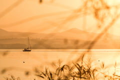 Golden sunset on a lake with a little boat Royalty Free Stock Images