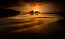 Golden Sunset at low tide, Holywell Bay, Cornwall, UK. Golden Sunset at low tide, with beautiful light reflecting on beach, Holywell Bay, Cornwall, UK royalty free stock images