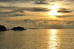 Sunset at the Maldives. Golden sunset at the Maldives with a bungalow in the Indian Ocean royalty free stock image