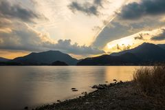 Lake surroundeb by wooded mountains at Sunset royalty free stock photography